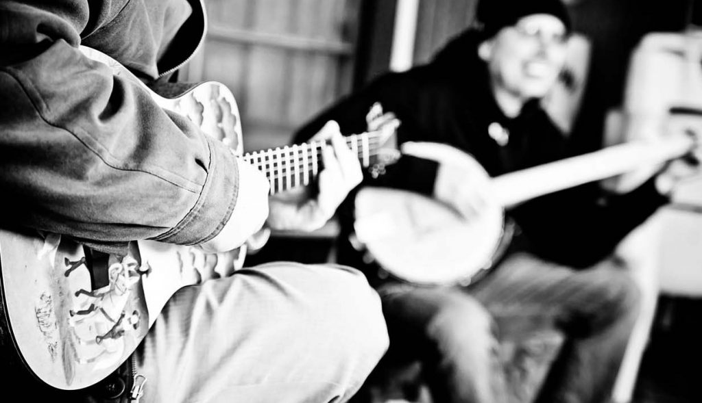 Two people playing guitar and banjo